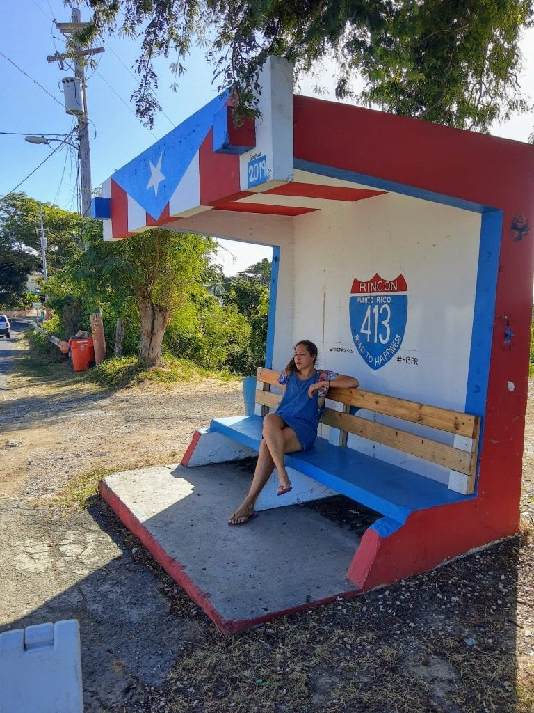 Route 413 in Rincon Puerto Rico, sarah fay sitting down at the bus stop.