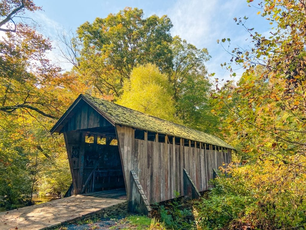 Things to Do in Charlotte, NC- pisgah covered bridge with beautiful fall foliage in background.