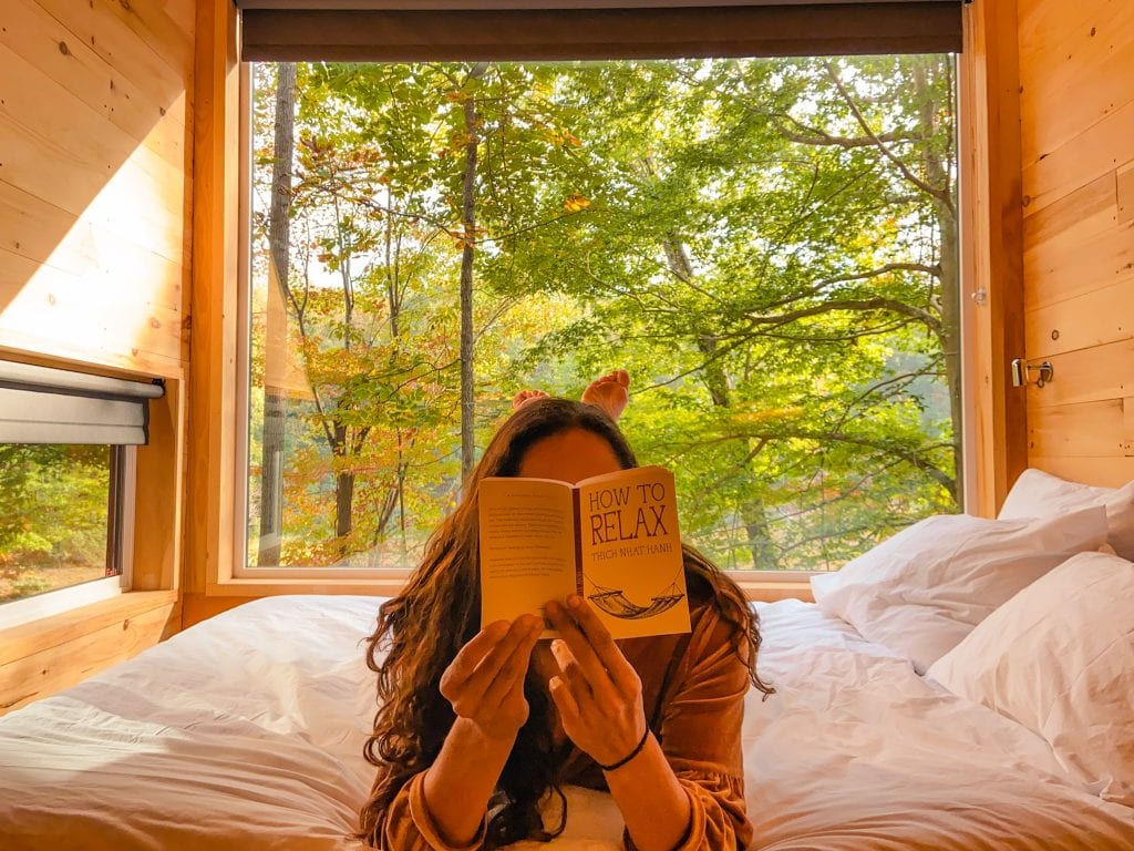 How to Relax at your Getaway House? Getaway House Review on the experience of glamping at Getaway. Travels of Sarah Fay reading on the bed with a giant window overlooking fall foliage and a lake!