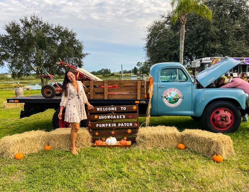 Pumpkin Patch at the Pumpkin Ponderosa at The Showcase of Citrus. Pumpkins sit on haystacks in front of a blue truck, with Sarah Fay travel blogger posing in front of the truck.