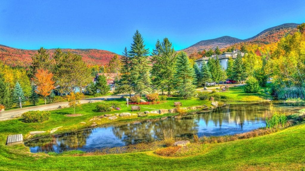 Fall foliage in New England at Stowe Vermont with a beautiful pond reflecting the trees in the water.