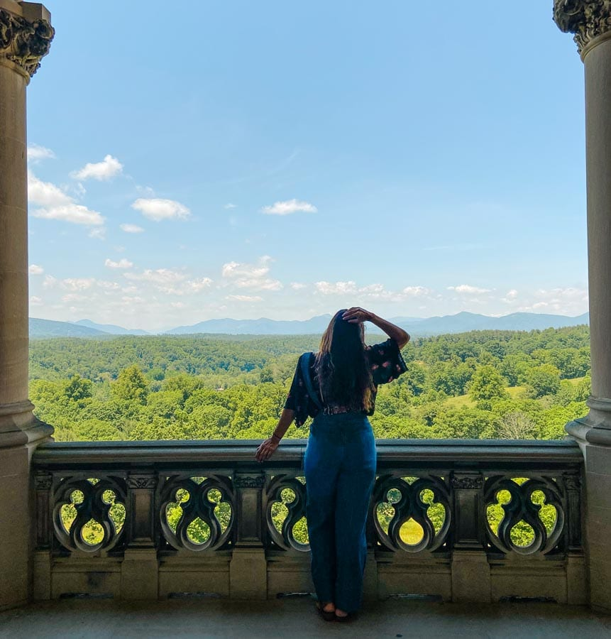 Sarah Fay standing on the back porch of the Biltmore Estate looking out onto Pisgah National Forest.