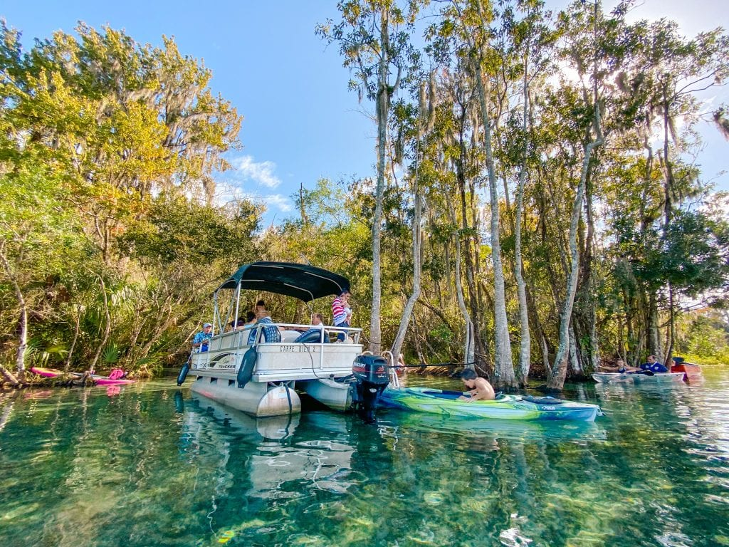 Florida's Best State Parks, Rainbow springs offers clear blue water where boats are resting in the water and enjoying the beautiful sunny days shaded under trees.