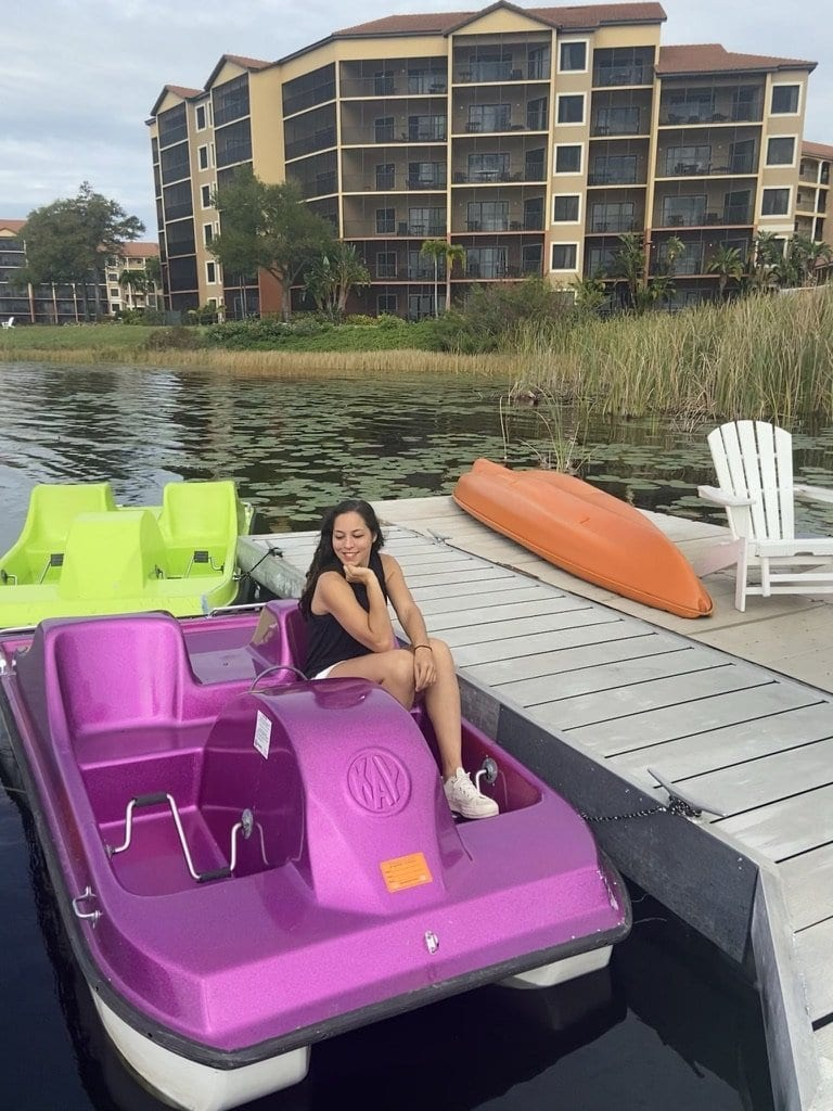 Sarah Fay travel blogger sitting in paddle boat ready to head out on the lake at Westgate Lakes Resort and Spa in Orlando, Florida.