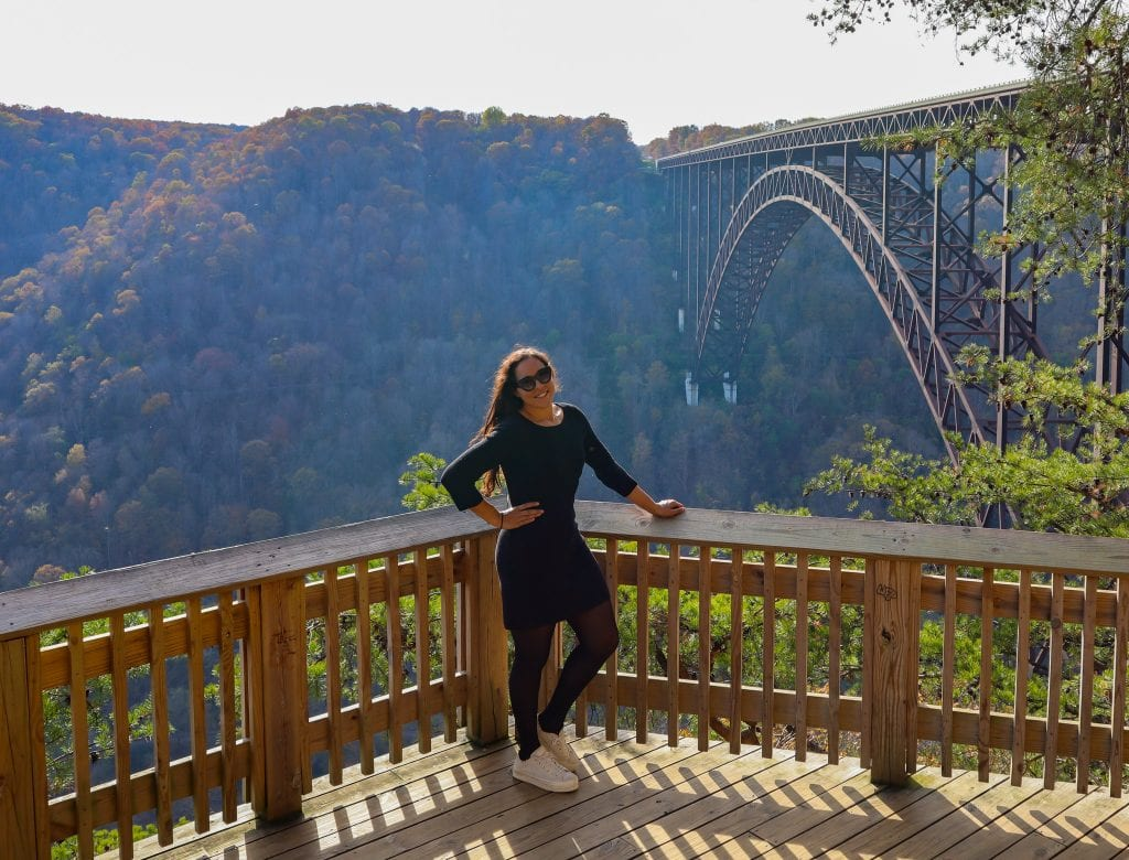 New River Gorge Bridge and lookout with Sarah Fay travel blogger in front of the beautiful fall colored leafs.