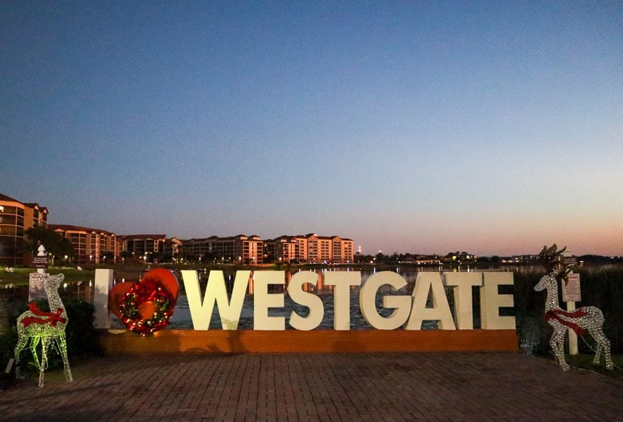 Westgate Lakes Resort and Spa sign decorated for christmas with a beautiful sunset hitting the buildings.
