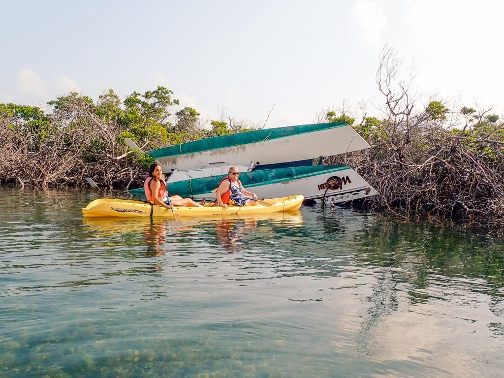 Catamaran boat damaged from hurricane upside down in a mangrove. Sarah Fay travel blogger and her mom paddling in a yellow kayak. Kayaking is a top thing to do in St. Thomas.