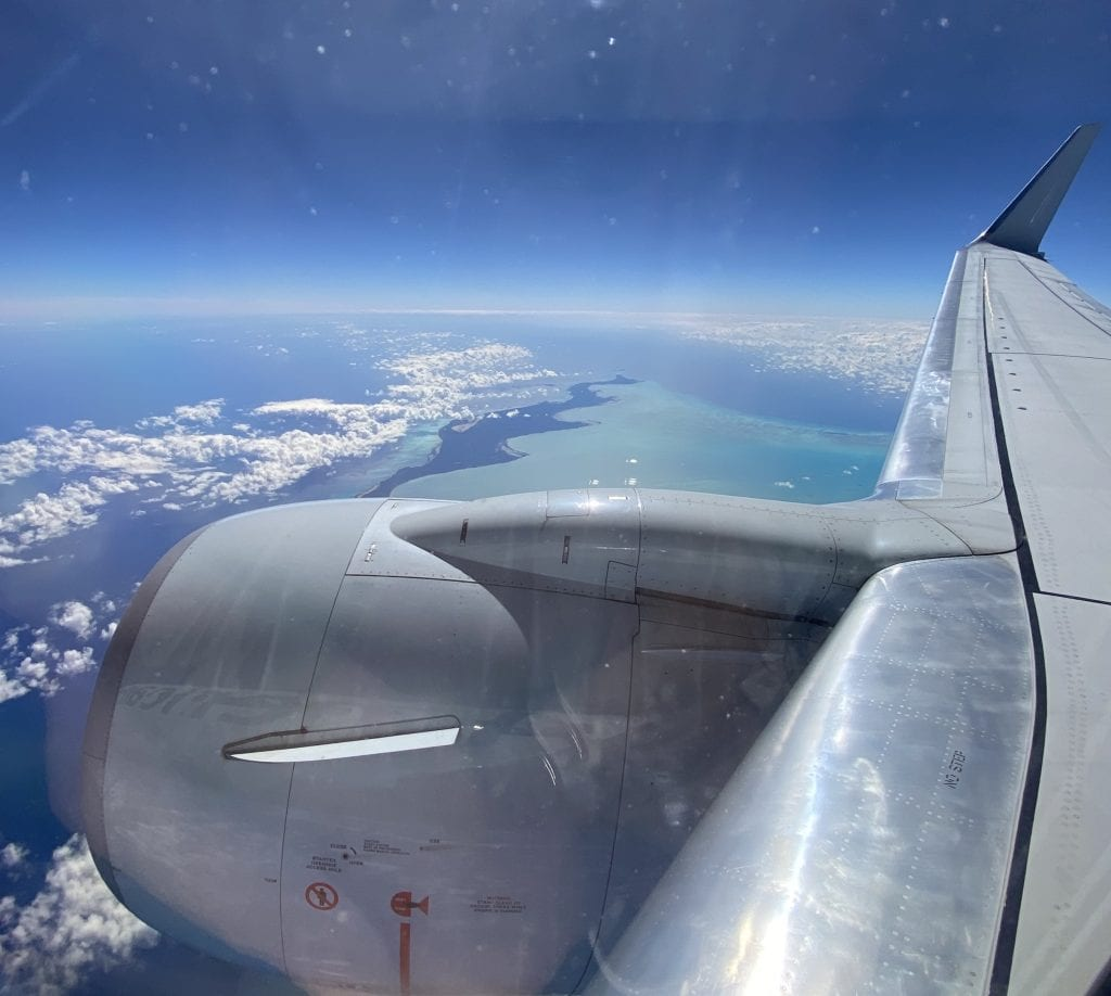 Flight with Caribbean Islands below and blue water with plane wing. One of the best things to do in st. Thomas is fly in or out on a sunny day to get some beautiful photos from the plane window.