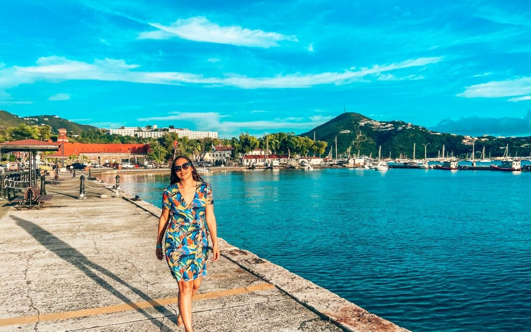 Sarah Fay travel blogger in floral dress walking down the malecon along the waterfront in Charlotte Amalie